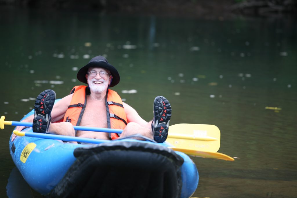 Man smiling slouching on boat on a river