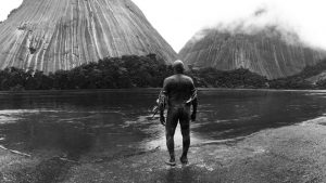 Indigenous man standing on river